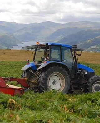 Tractor harvesting bracken for Lakeland Gold Compost